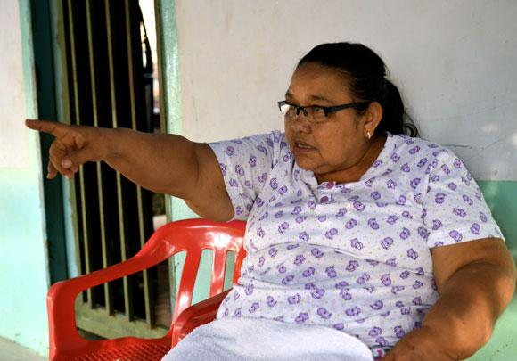 Marina López sentada afuera de su tienda, señala al horizonte el lugar donde por última vez sus vecinos le dijeron haber visto a sus hijos Alexandra y Diego Fernando.