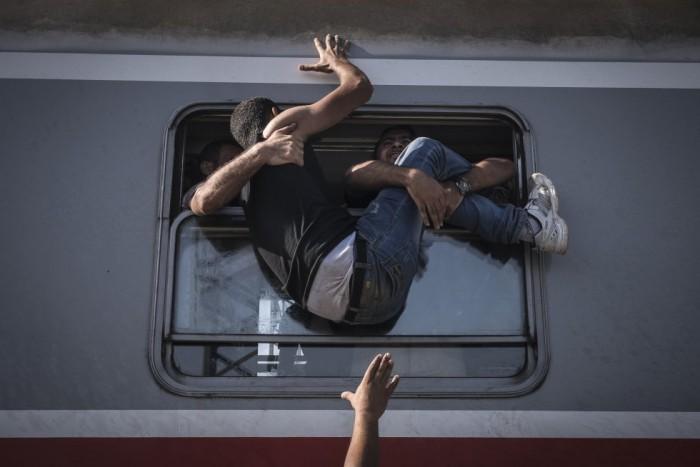 Sergey Ponomarev, del 'The New York Times', ha sido reconocido con el primer premio de la categoría de Historias de Temas Generales con esta foto de un grupo de refugiados intentando subir a un tren hacia Zagreb, desde Tovarnik, en Croacia. SERGEY PONOMAREV (AP)