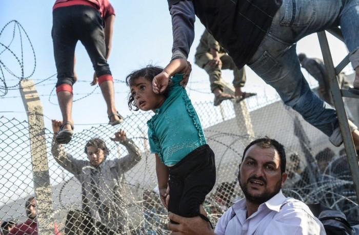 Esta foto, publicada en junio en EL PAÍS y otros medios internacionales, corresponde a uno de los episodios más tensos de la crisis de refugiados sirios. Los asilados entran en Turquia tras romper la valla que le separa de Siria. Es el tercer premio en el apartado de historias TERCER PREMIO EN HISTORIAS DE NOTICIAS DE ACTUALIDAD BULENT KILIC (AFP)