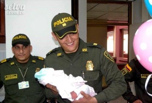 El comandante Palacios sosteniendo a la niña indígena que él ayudó a nacer