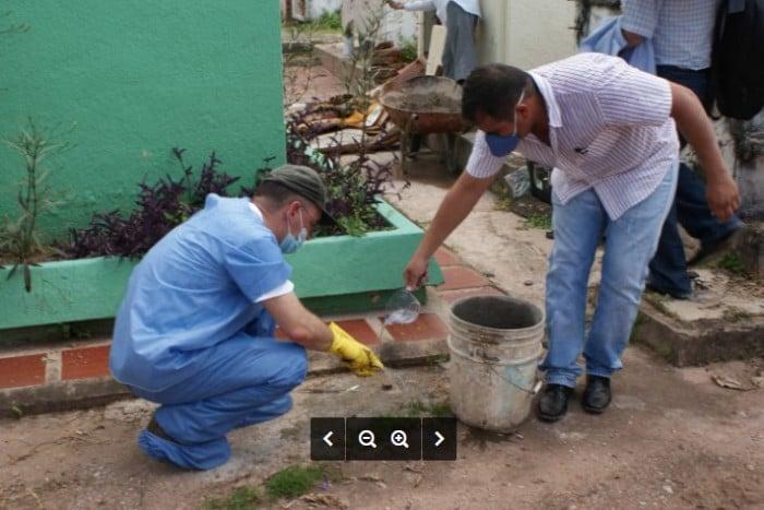 Esta es una de las 210 fotografías que documentan la exhumación de Máximo Duque. Se le ve trabajando en piso destapado, con un balde de construcción un asistente sin guantes, cuando lavan una pieza con agua.