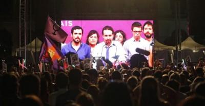 Simpatizantes de Unidos Podemos escuchan las declaraciones de su líder Pablo Iglesias (c. en la pantalla) durante su comparecencia ante la prensa tras conocer los resultados de las elecciones generales celebradas en España, este domingo en la plaza del museo Reina Sofía de Madrid. EFE/Kiko Huesca